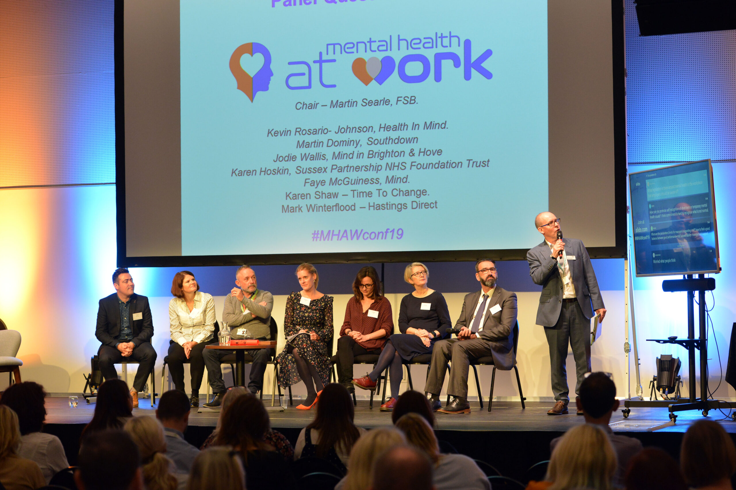 Picture of a person delivering a presentation on a conference stage, next to a panel of specialists