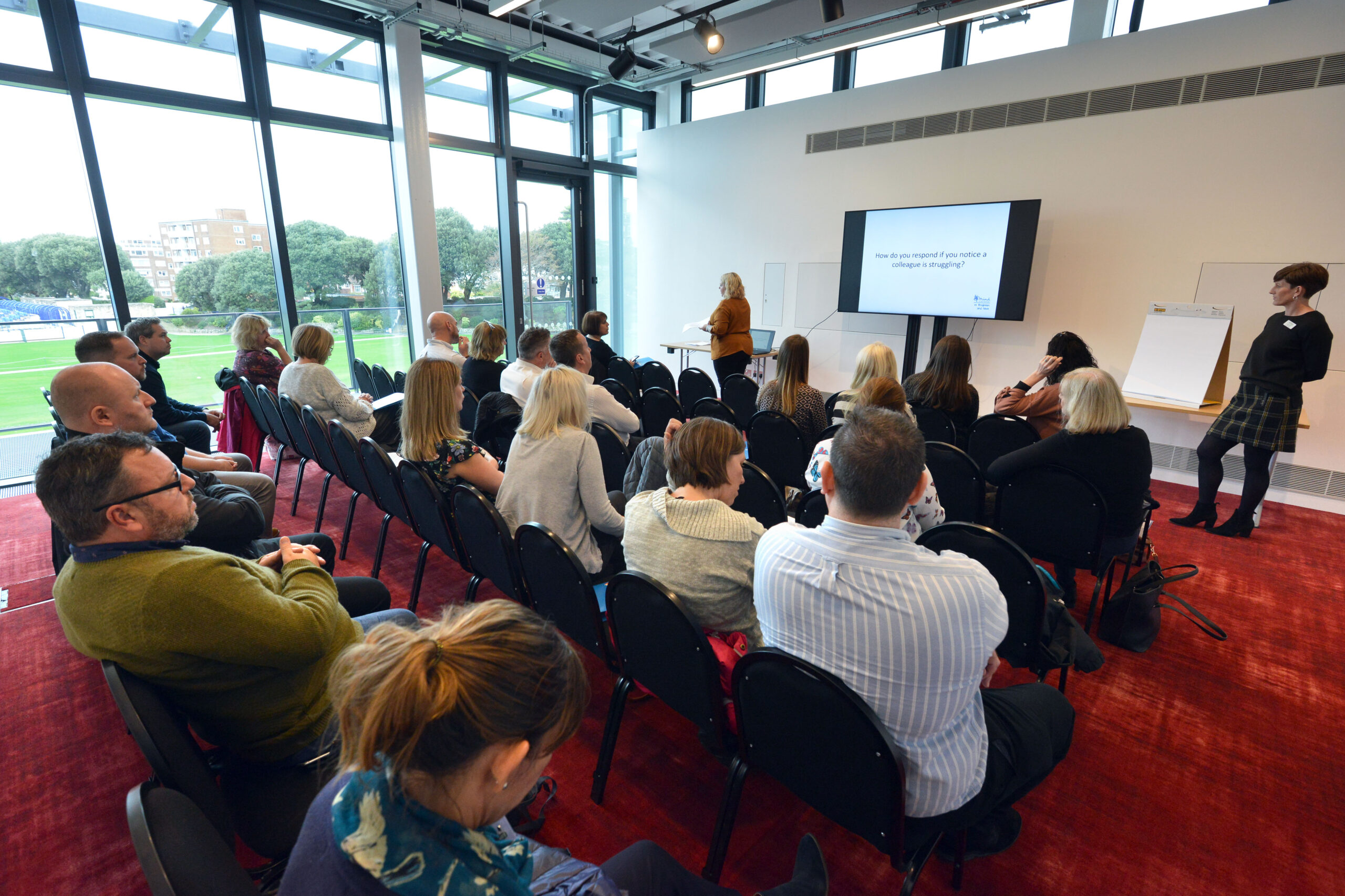 Photo of a conference room with participants looking at the presentation screen