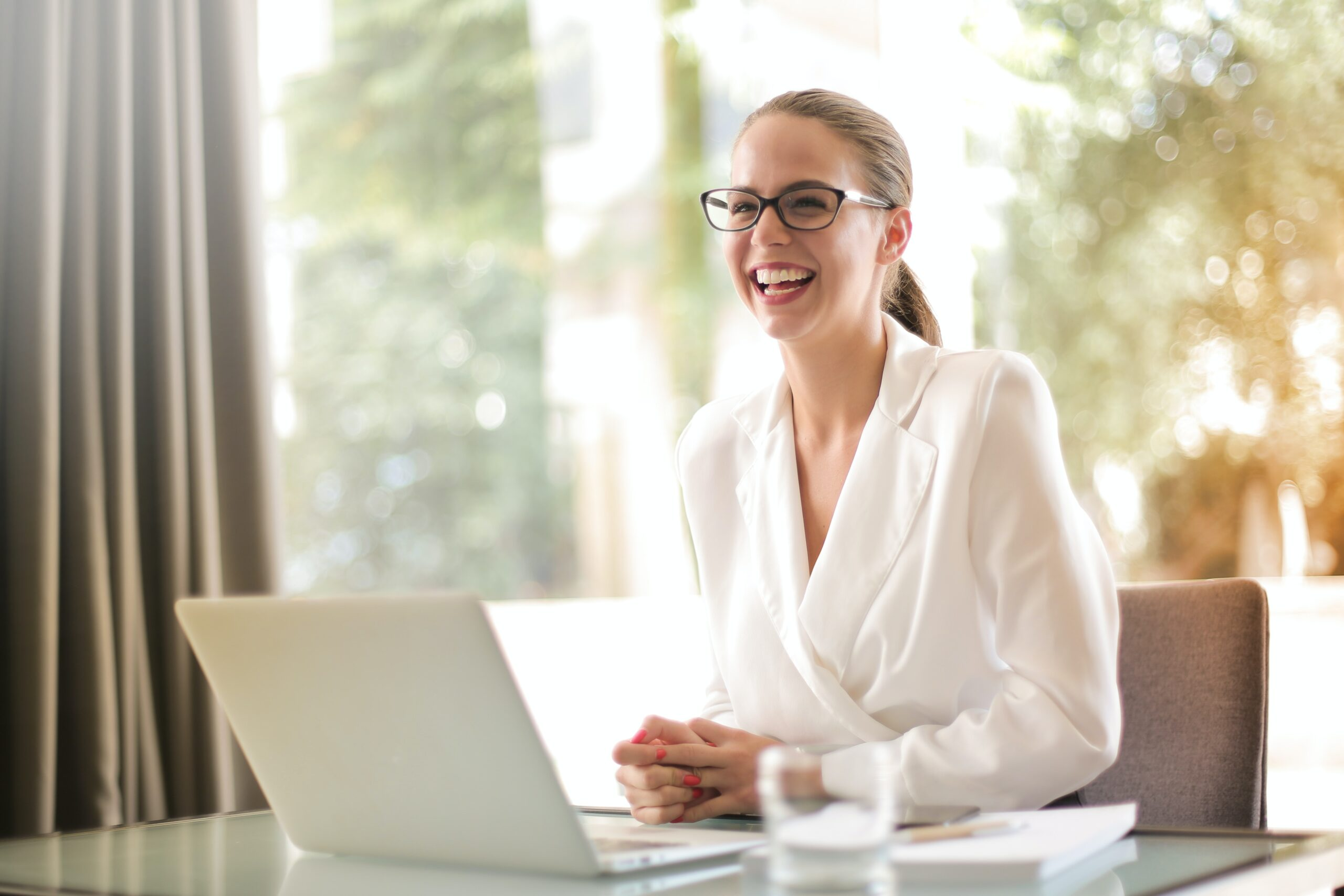 Woman smiling, sat at a desk in front of her laptop