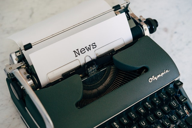 Picture of a typewriter with a sheet of paper with the word 'news' typed on it