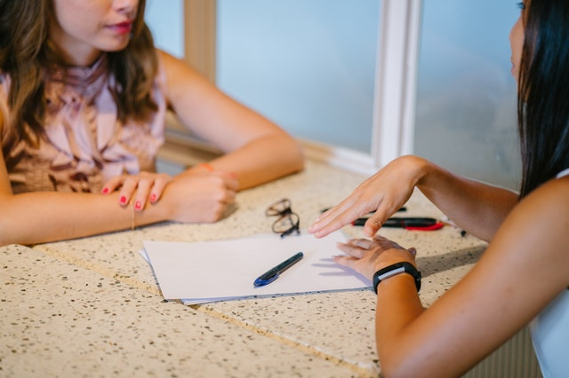 Picture of two women sat at a table talking to each other and making some notes
